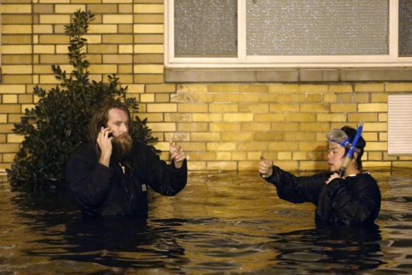 A man in snorkelling gear and his friend wade through the flooded streets of Brooklyn, New York, on Monday