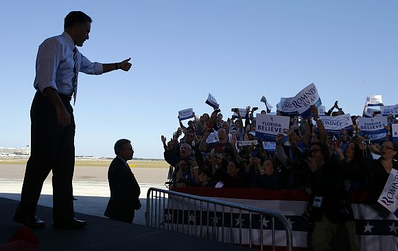 Romney gives a thumbs up to the cheering crowd as he takes the stage