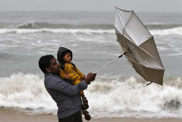 A man carrying his child tries to hold an umbrella at Marina beach in Chennai
