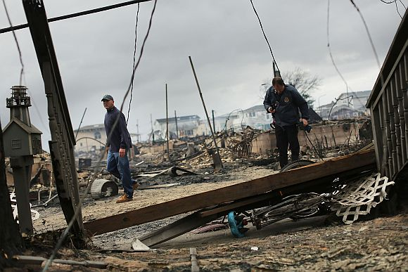Fire inspectors walk through a neighborhood destroyed during Hurricane Sandy in the Breezy Point neighborhood of the Queens borough of New York City