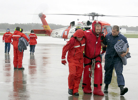 Members of the Coast Guard assist one of the sailors to the runway at the Air Station Elizabeth City, North Carolina. The US Coast Guard rescued 14 of the 16 crew members who abandoned the HMS Bounty off North Carolina in rough seas caused by Hurricane Sandy