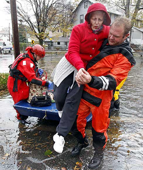 An emergency personnel lifts an elderly resident out of a rescue boat to dry land away from flood waters brought on by Hurricane Sandy in Little Ferry, New Jersey