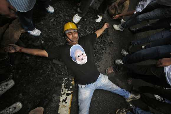 An activist from Bharatiya Janata Yuva Morcha, wearing a cut-out of India's Prime Minister Manmohan Singh, lies on a heap of charcoal during a protest in New Delhi August. The protesters were demanding the resignation of Singh over his government's role in an affair dubbed coal-gate