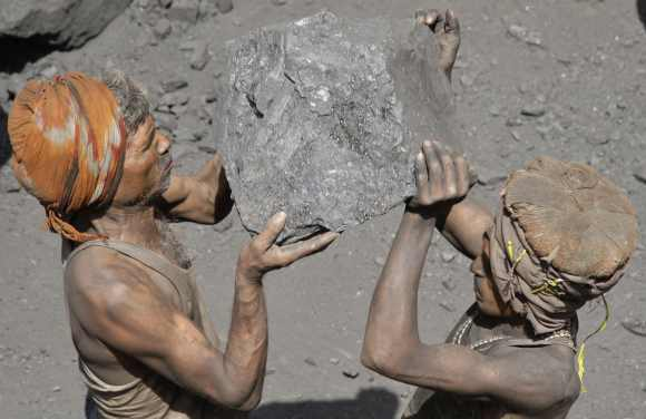 Labourers carry coal to load onto a truck at a coal yard on the outskirts of the northern Indian city of Allahabad
