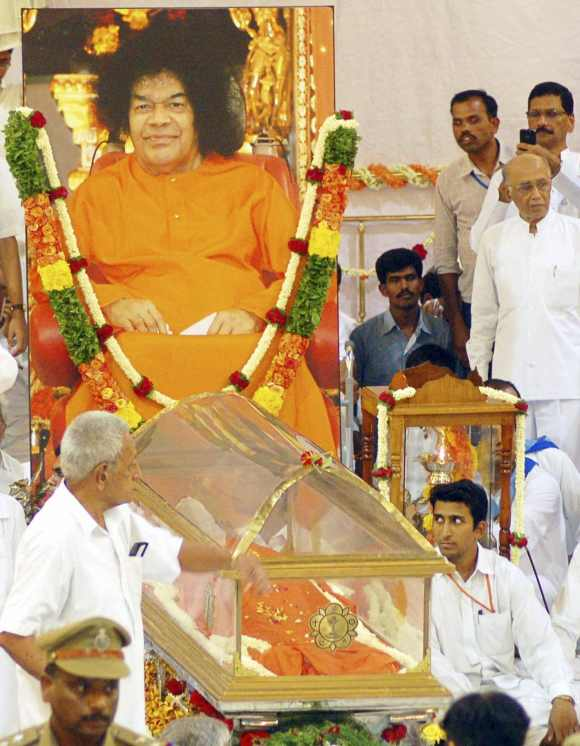 Devotees sit beside the body of spiritual guru Sri Sathya Sai Baba at an ashram at Puttaparti, Andhra Pradesh on April 24, 2011