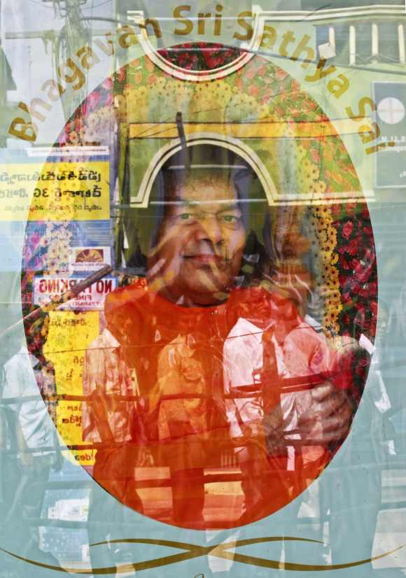 Devotees are reflected in a the window of a shop displaying a photograph of spiritual guru Sri Sathya Sai Baba