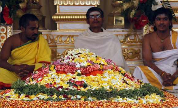 Hindu priests chant hymns by the grave of spiritual guru Sri Sathya Sai Baba inside an ashram at Puttaparti