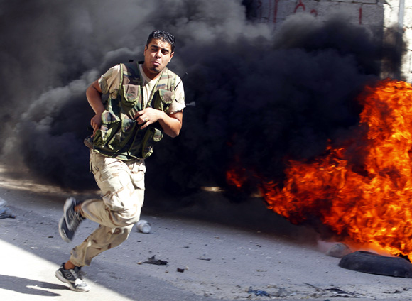 A Free Syrian Army fighter runs across a street dodging Syrian army bullets in El Amreeyeh neighbourhood of Syri