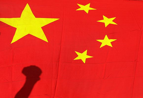 Shadow of clenched fist of protester is seen on Chinese national flag during anti-Japan protest in Beijing