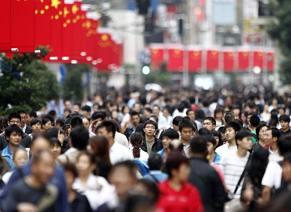 People walk next to Chinese flags at a pedestrian section of Nanjing road in Shanghai