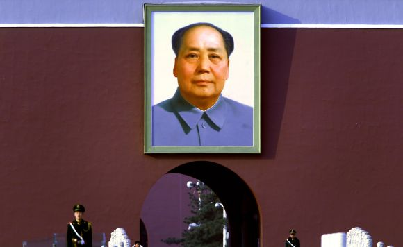 Paramilitary policeman stand guard underneath the giant portrait of Mao on Beijing's Tiananmen Square
