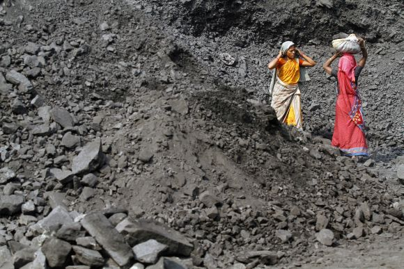 Labourers carry coal at a stockyard of an underground coal mine in Odisha