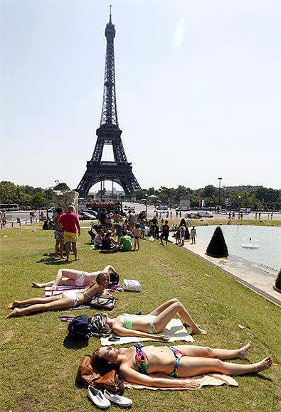 People sunbathe on the grass near the Eiffel Tower, Paris