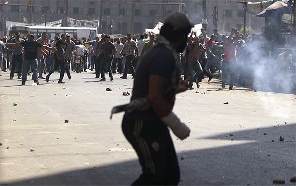 Anti-Mursi protesters run as supporters of Egypt's President Mohamed Mursi throw stones at each other during clashes in Tahrir Square in Cairo