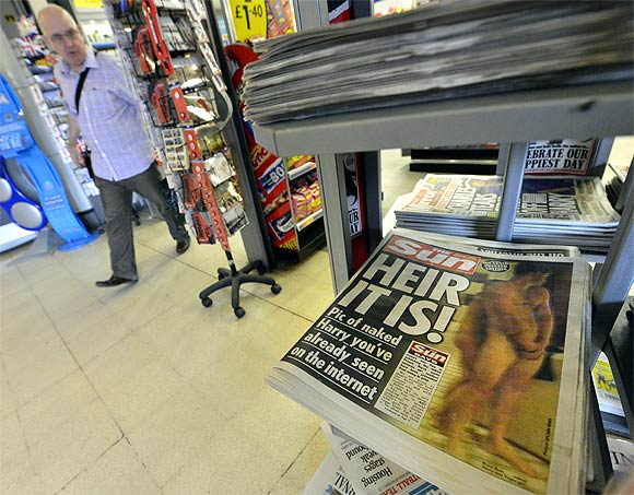 A newstand displays copies of 'The Sun' newspaper featuring a picture of a naked Prince Harry