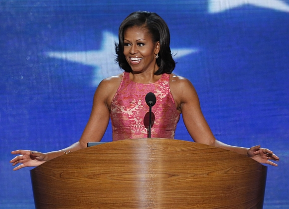 US first lady Michelle Obama smiles as she arrives to address delegates during the first session