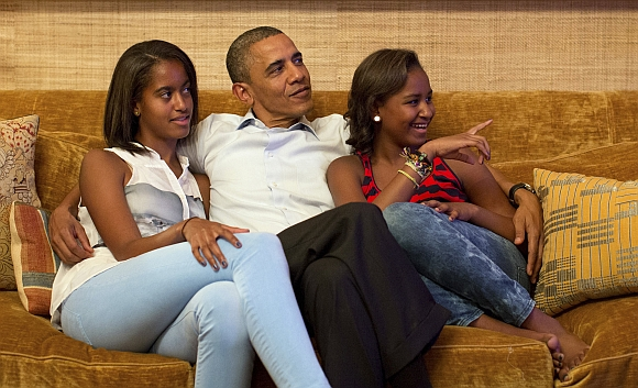 US President Barack Obama and his daughters Malia (left) and Sasha, watch on television as first lady Michelle Obama takes the stage to deliver her speech at the Democratic National Convention, in the Treaty Room of the White House in Washington September