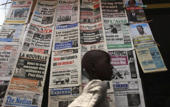A boy walks past a newspaper kiosk at the Carrefour Wada district in Cameroonian capital Yaounde