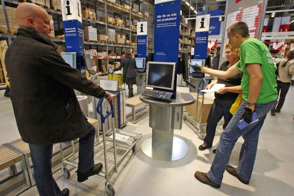 Customers check products on computer terminals at a store in Malmo, Sweden