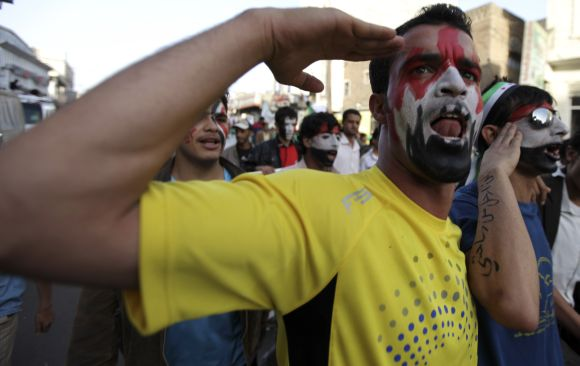 An anti-government protester gestures with the colours of the national flag of Yemen on his face during a demonstration in Sanaa.