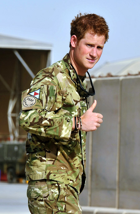 Britain's Prince Harry gestures after passing the Apache helicopter flight line at Camp Bastion, Afghanistan