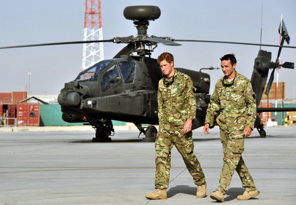 Prince Harry is shown the Apache helicopter flight line by an unidentified member of his squadron at Camp Bastion, Afghanistan