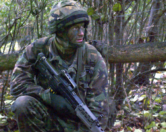 Prince Harry crouches during an exercise in the UK