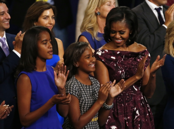 First Lady Michelle Obama applauds with daughters Malia and Sasha