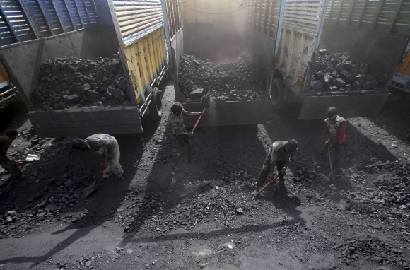 Labourers load coal onto trucks at a coal yard