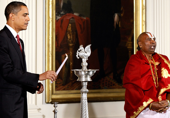 US President Barack Obama lights a traditional oil lamp as Sri Narayanachar Digalakote, Hindu priest from the Sri Siva Vishnu Temple in Maryland, chants in observance of Diwali in the East Room at the White House October 14, 2009 in Washington, DC