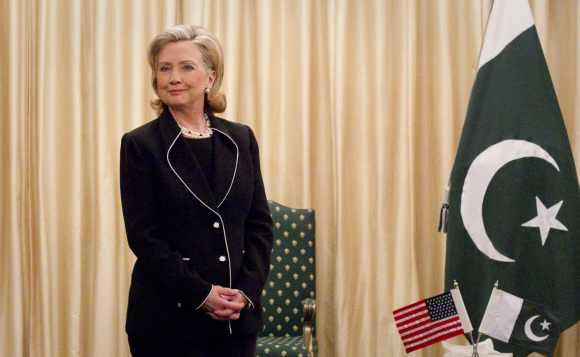 US Secretary of State Hillary Clinton stands next to the Pakistan national flag