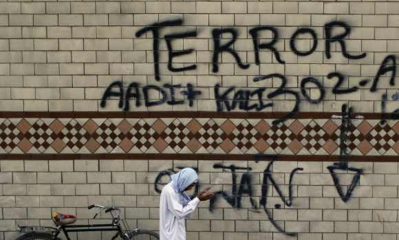 A man prays, next to graffiti painted road-side, during a anti-Taliban rally in Rawalpindi