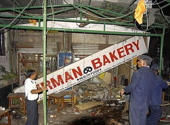 Firefighters examine the site of a bomb blast at the German Bakery restaurant in Pune on February 13, 2010