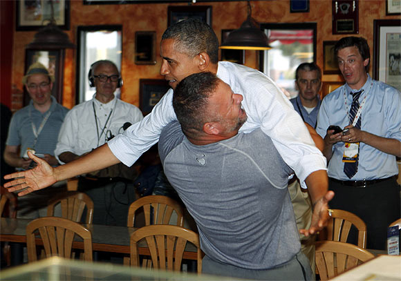 US President Barack Obama holds on as he is hugged and picked up by Scott Van Duzer at Big Apple Pizza and Pasta Italian Restaurant in Fort Pierce, Florida, while campaigning across the state by bus