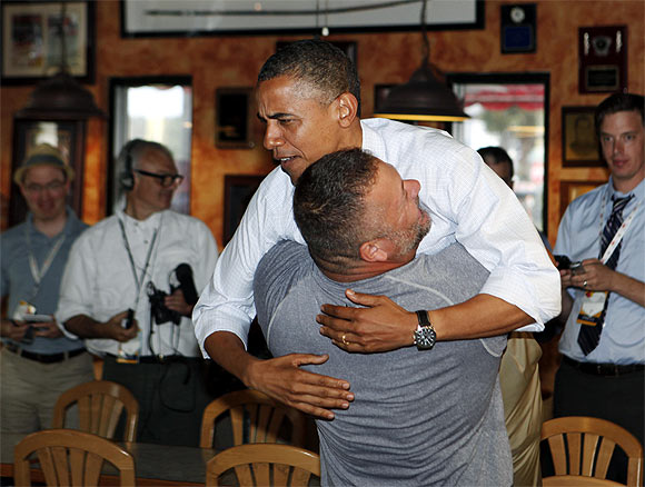 Obama holds on as he is hugged and picked up by Scott Van Duzer at Big Apple Pizza and Pasta Italian Restaurant