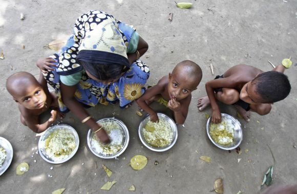 Villagers affected by ethnic riots eat their community lunch inside a relief camp near Bilasipara town in Assam