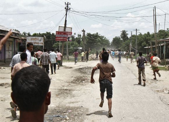 Villagers affected by ethnic riots run after the Assam legislative assembly team during their visit at a relief camp in Assam
