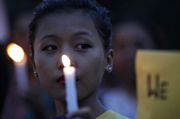 Woman holds candle during vigil to show solidarity with the people of Assam at a rally in front of the India Gate in New Delhi