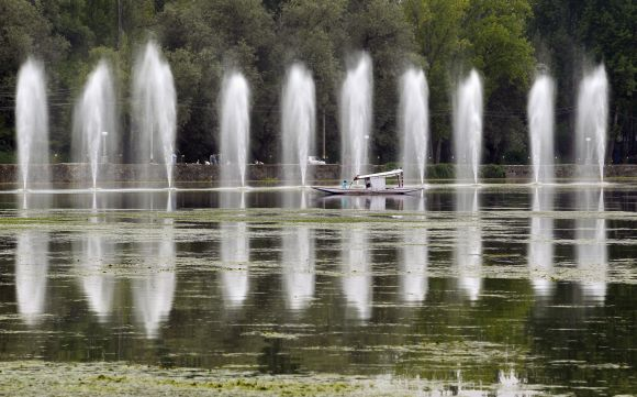 A Kashmiri man rows a boat past fountains in the polluted waters of Dal Lake, in Srinagar