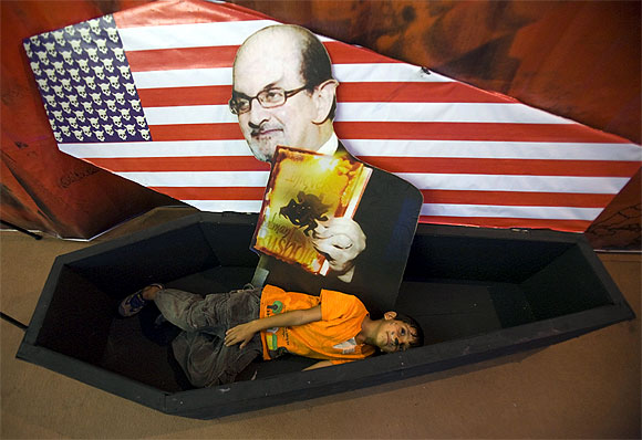 An Iranian boy lies in a symbolic coffin for the US with a picture of author Salman Rushdie