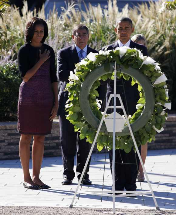 US President Barack Obama is joined by first lady Michelle Obama and US Secretary of Defence Leon Panetta as he lays a wreath during a memorial