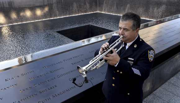 New York City police bugler Gabe Perdomo warms up while standing next to the South Pool