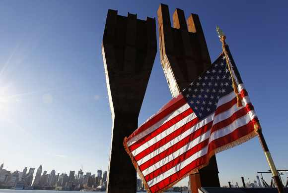 A US flag flies at a memorial bearing two pieces of steel from the World Trade Center in Weehawken, New Jersey, across from the skyline of New York