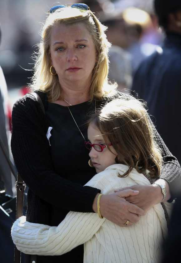 Nina Fisher, sister of 9/11 victim Andrew Fisher, embraces her niece Mia Tinson, 9, during a ceremony at the WTC