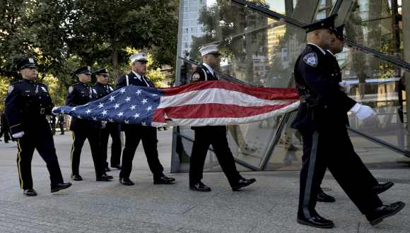 Port Authority Police Officers carry the US flag that flew at the World Trade Center towers during a 9/11 ceremony