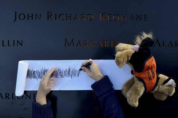 Ava Kathleen Schmoelzer, 7, makes a rubbing of her late aunt's name, Kathleen Moran at the WTC