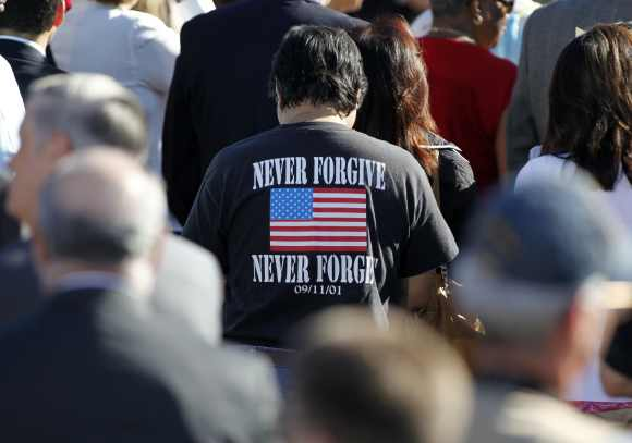 A man wears a t-shirt which honours those who died during the attacks of September 11, 2001 during a memorial service
