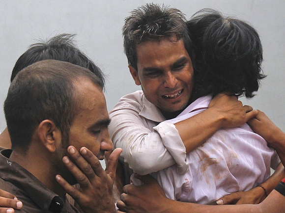 Relatives mourn their loved ones, who were killed in a fire at a garment factory, after their bodies were brought to the Jinnah hospital morgue in Karachi