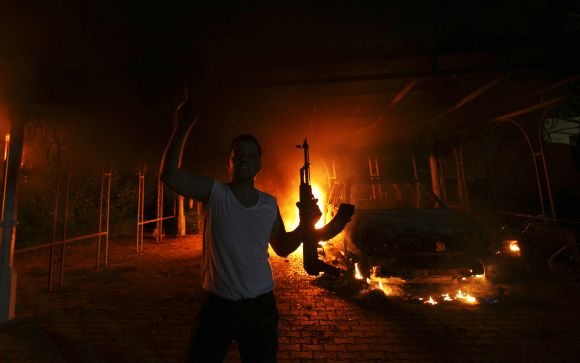 A protester reacts as the US consulate in Benghazi is seen in flames