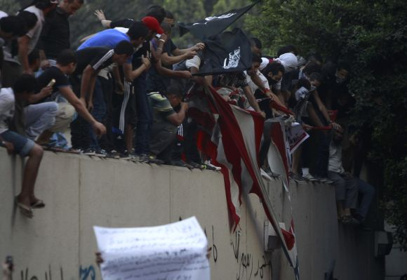 Protesters destroy an American flag pulled down from the US embassy in Cairo
